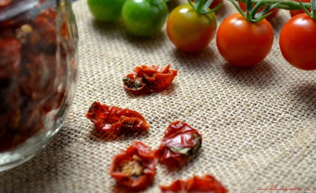 A close up shot of sun dried cherry tomatoes. In the background, fresh cherry tomatoes can be seen.