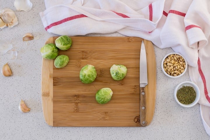 Brussels sprouts on a wooden board about to be sliced in half with a knife.