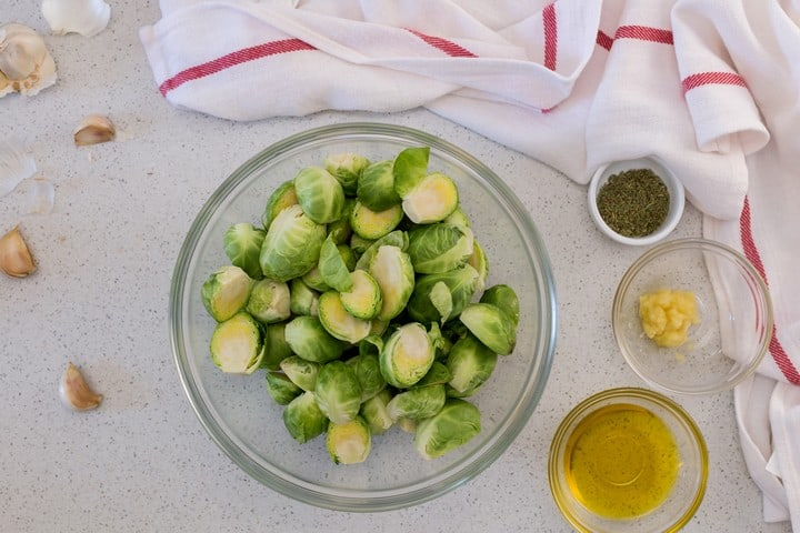 Brussels sprouts in a bowl surrounded by olive oil, garlic and rosemary.
