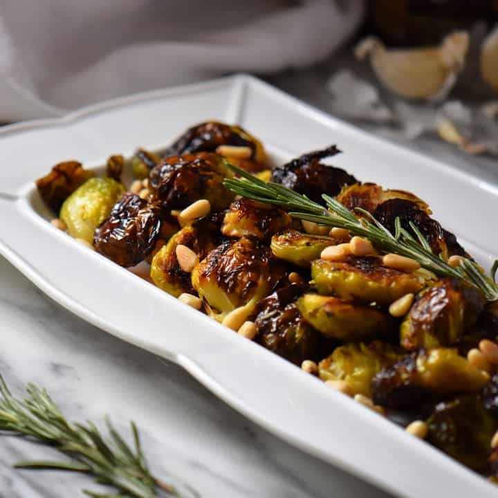 Roasted Brussels sprouts on a white dish, topped with fresh rosemary and roasted pine nuts.