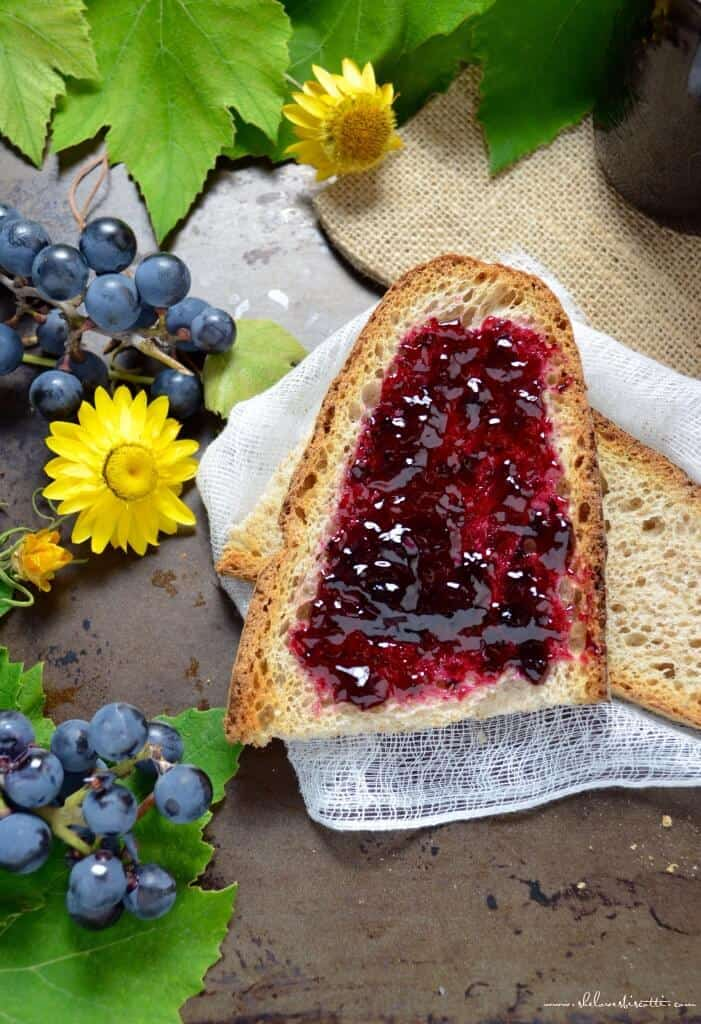 An overhead shot of concord grape jelly spread on a piece of whole wheat bread.