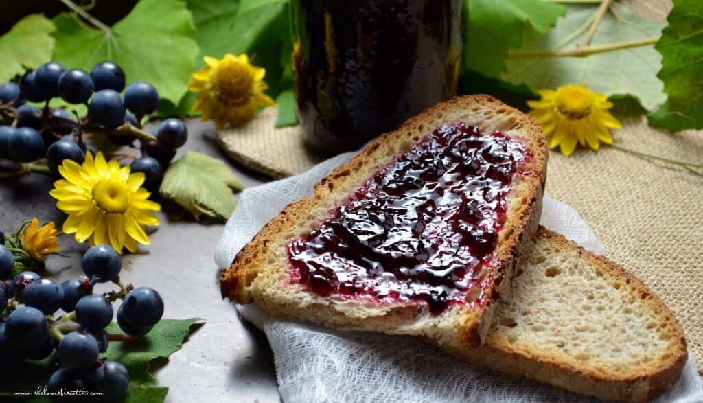 Grape jelly spread across a slice of brown bread.