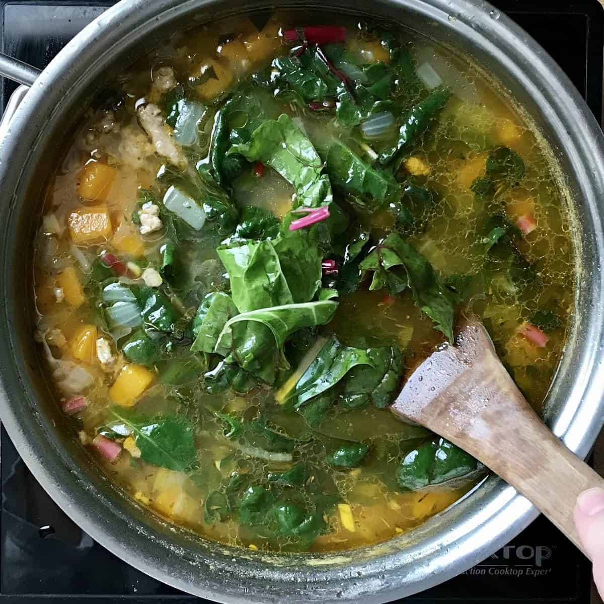 Swiss chard being added to the stockpot.