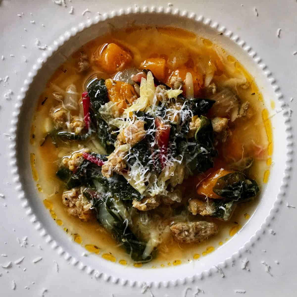 An overhead photo of Italian sausage squash soup and swiss chard with grated cheese