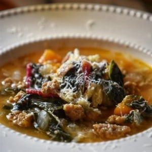 Italian Sausage Squash Soup with swiss chard in a white bowl.