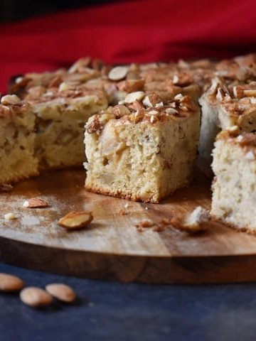 A few apple squares on a wooden board, surrounded by a few raw almonds.