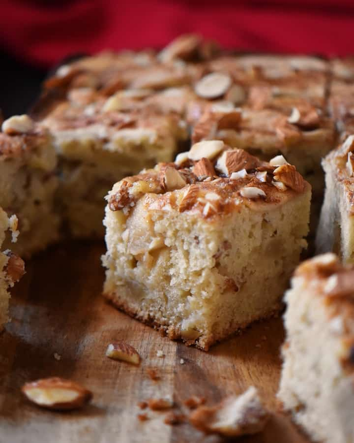 A square piece of apple cake with a crunchy almond topping.