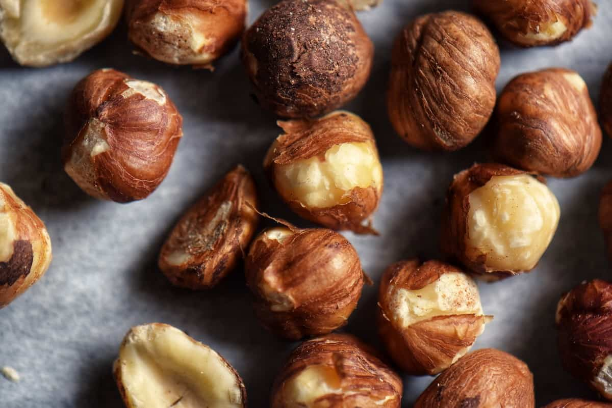 Freshly roasted hazelnuts with some of their skins removed.