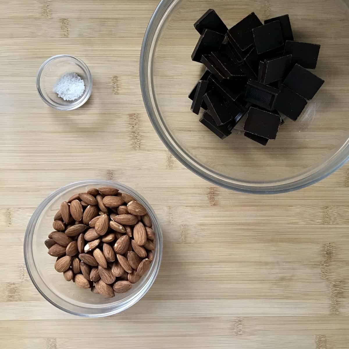 Chocolate, almonds and salt in separate bowls.