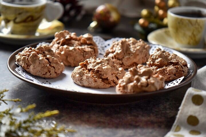 A tray of brutti ma buoni cookies on a table surrounded by Christmas decor.