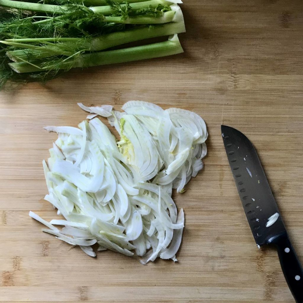 Thinly sliced fennel on a wooden board.