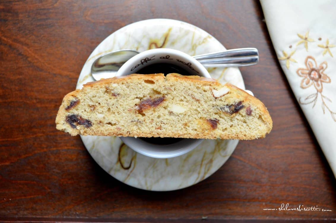 A sliced date biscotti set on an espresso cup.