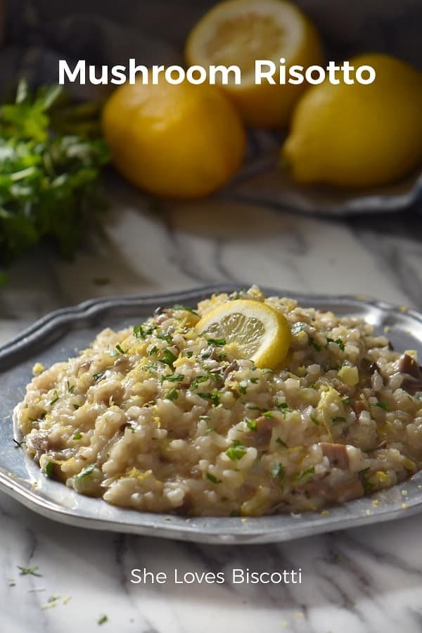 Mushroom Risotto in a pewter plate, topped with chopped parsley and a slice of lemon.
