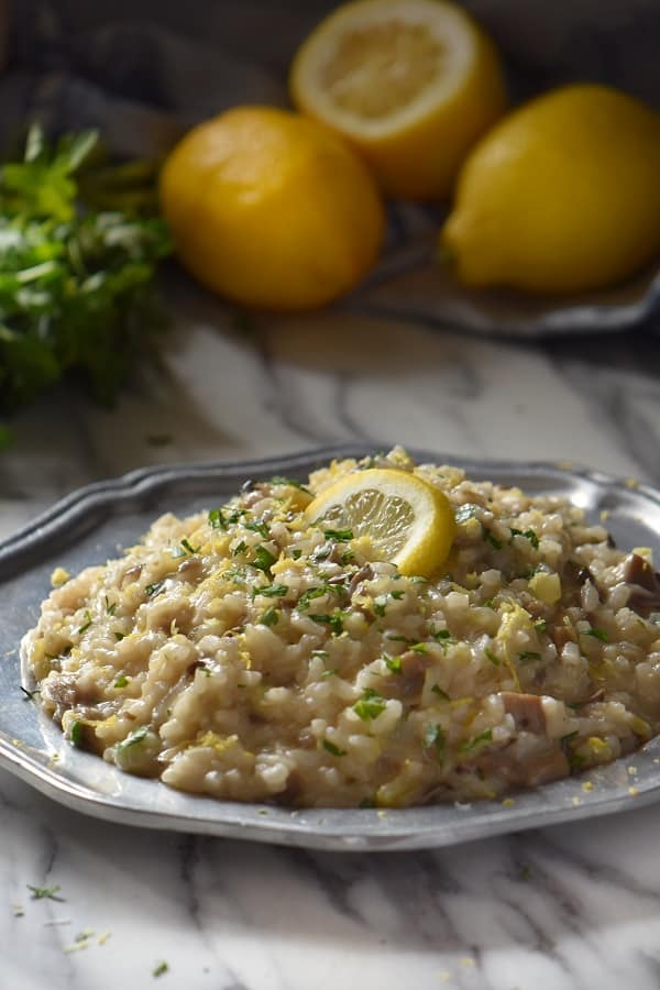 Creamy Mushroom Risotto in a pewter plate, topped with finely chopped parsley and a lemon slice. In the background, there are three whole lemons.