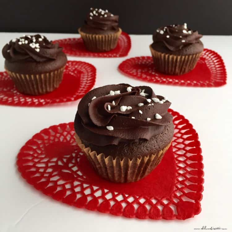 A few Chocolate Surprise Cupcakes on red doilies.