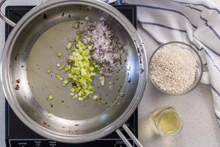 Celery and shallots being sauteed in a large pan.