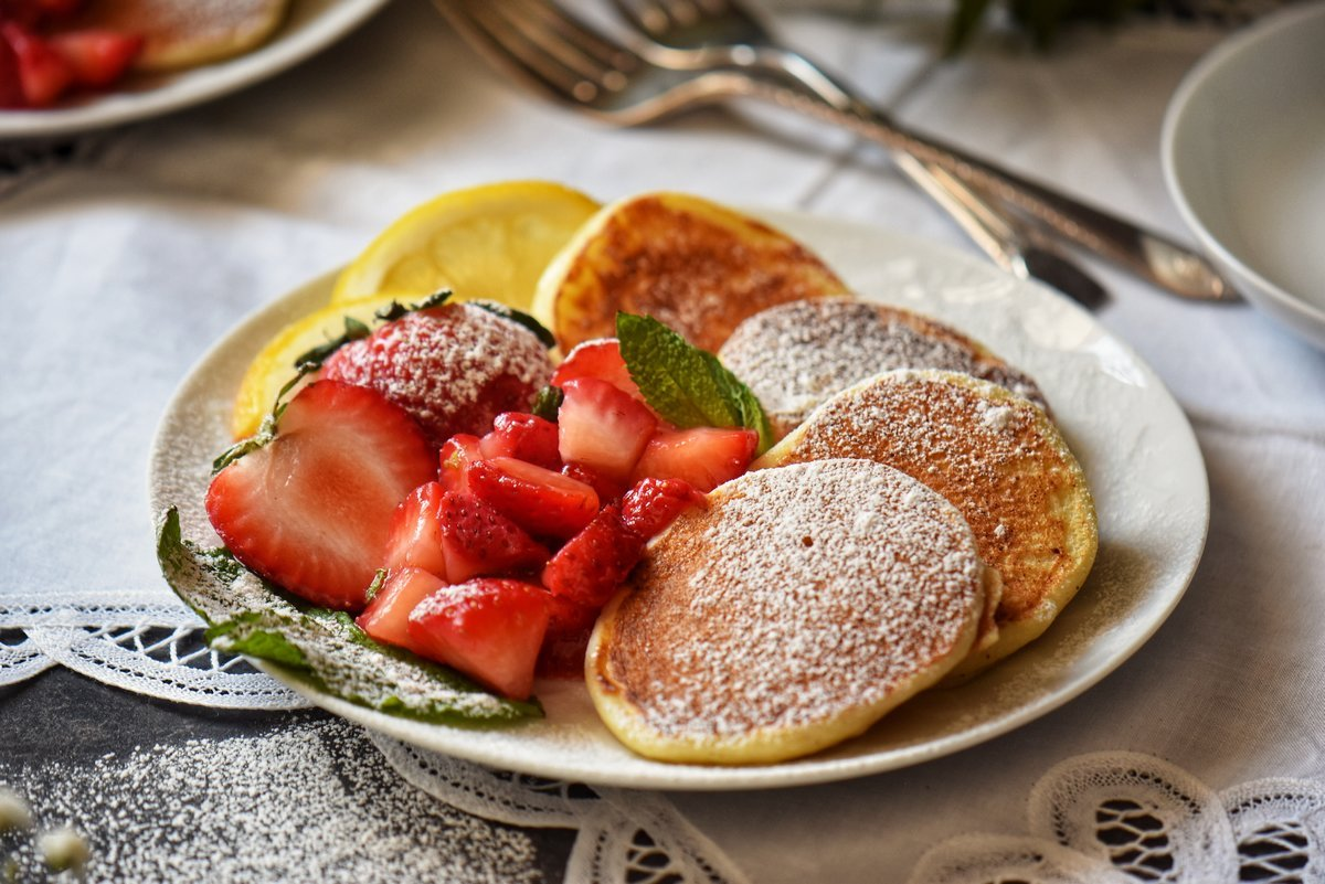 Macerated strawberries next to pancakes in a white plate.