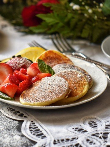 Lemon Ricotta Pancakes, lightly dusted with icing sugar, on a white plate.