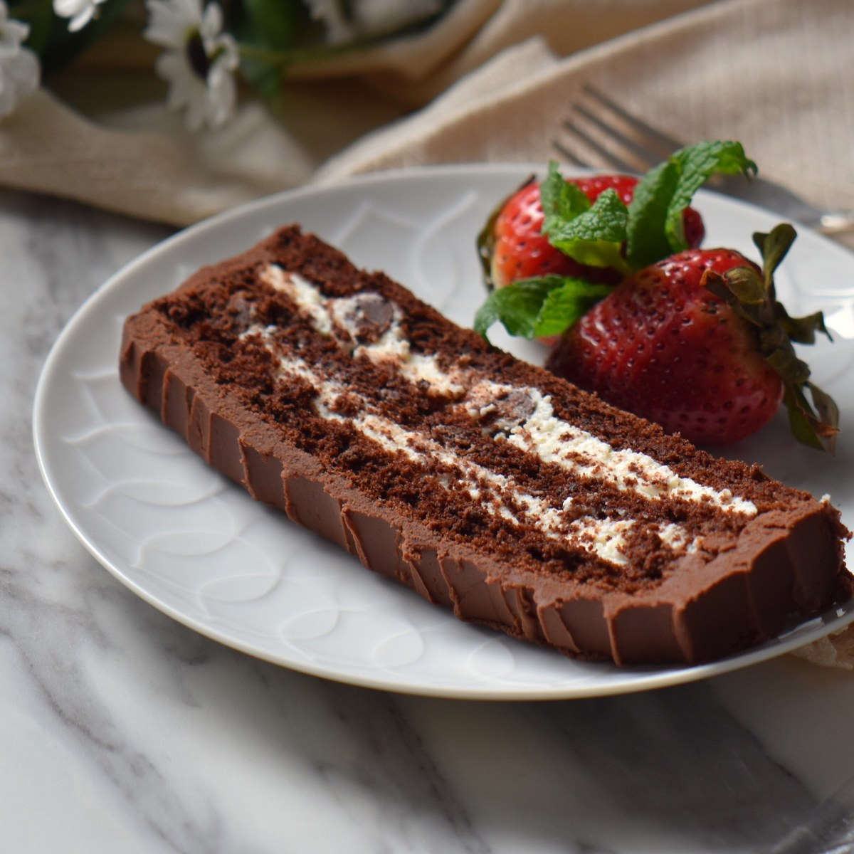 A slice of Chocolate Cream cake with strawberries on a white plate.