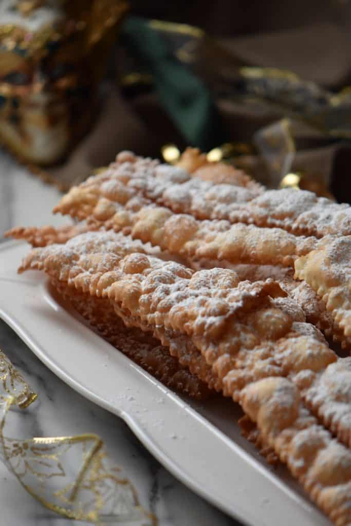 A light and crispy Italian cookie that can be called many names such as crostoli, chiacchiere and angel wings on a white serving platter.