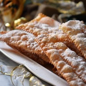 A close up shot of the dozens of tiny air pockets of this Italian fried Italian cookie (crostoli) can be seen.