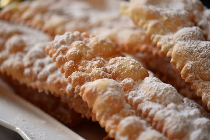 Italian fritters called frappe or crostoli dusted with icing sugar on a white serving platter.