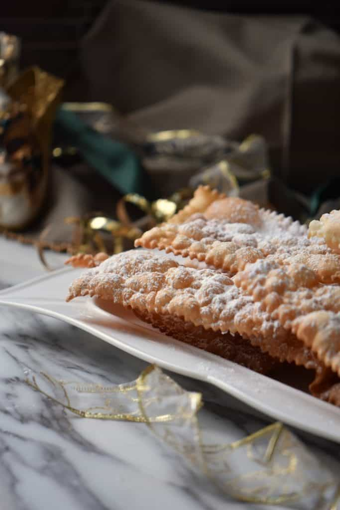 Festive looking crostoli (fried Italian ribbon cookies) on a white serving dish.
