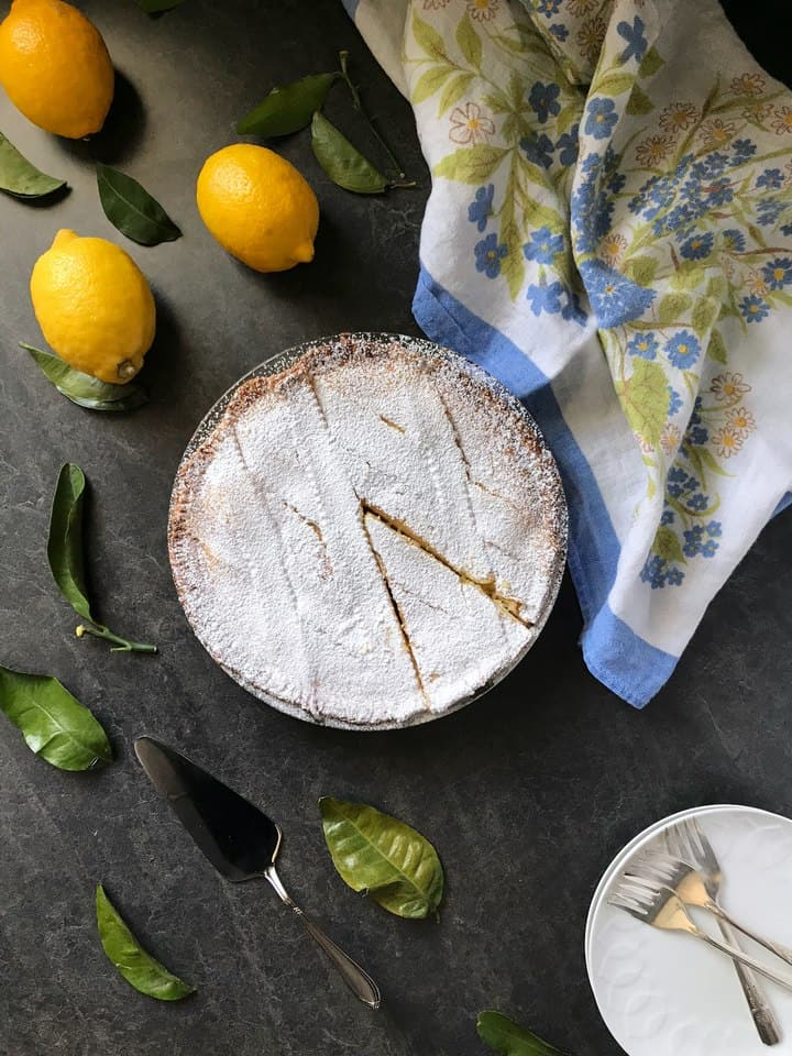 An overhead shot of a ricotta pie, dusted with icing sugar and surrounded by lemons and a floral tea towel.