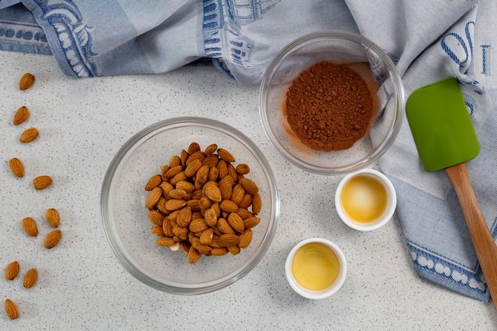 The ingredients required to make cocoa almonds in bowls.