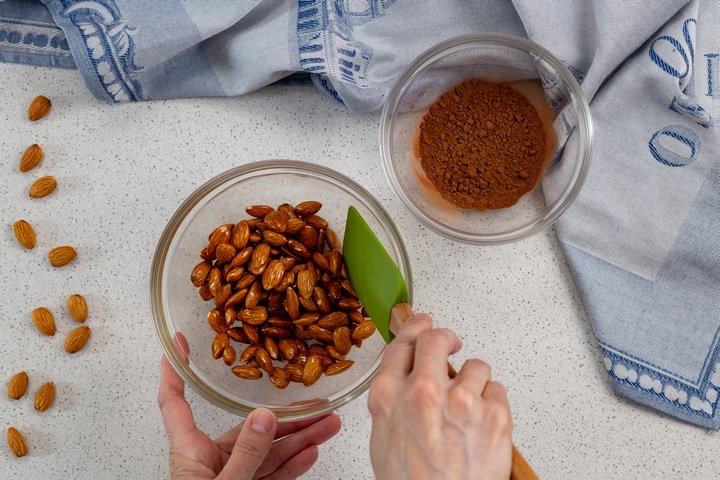 The honey mixture being combined with the almonds.