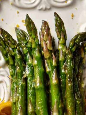 An overhead shot of sauteed asparagus garnished with lemon zest.