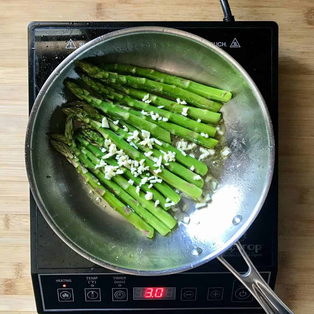 Sauteed asparagus with chopped garlic in a pan.