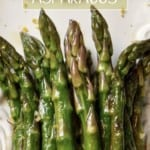 Sauteed asparagus garnished with lemon zest on a white serving dish.