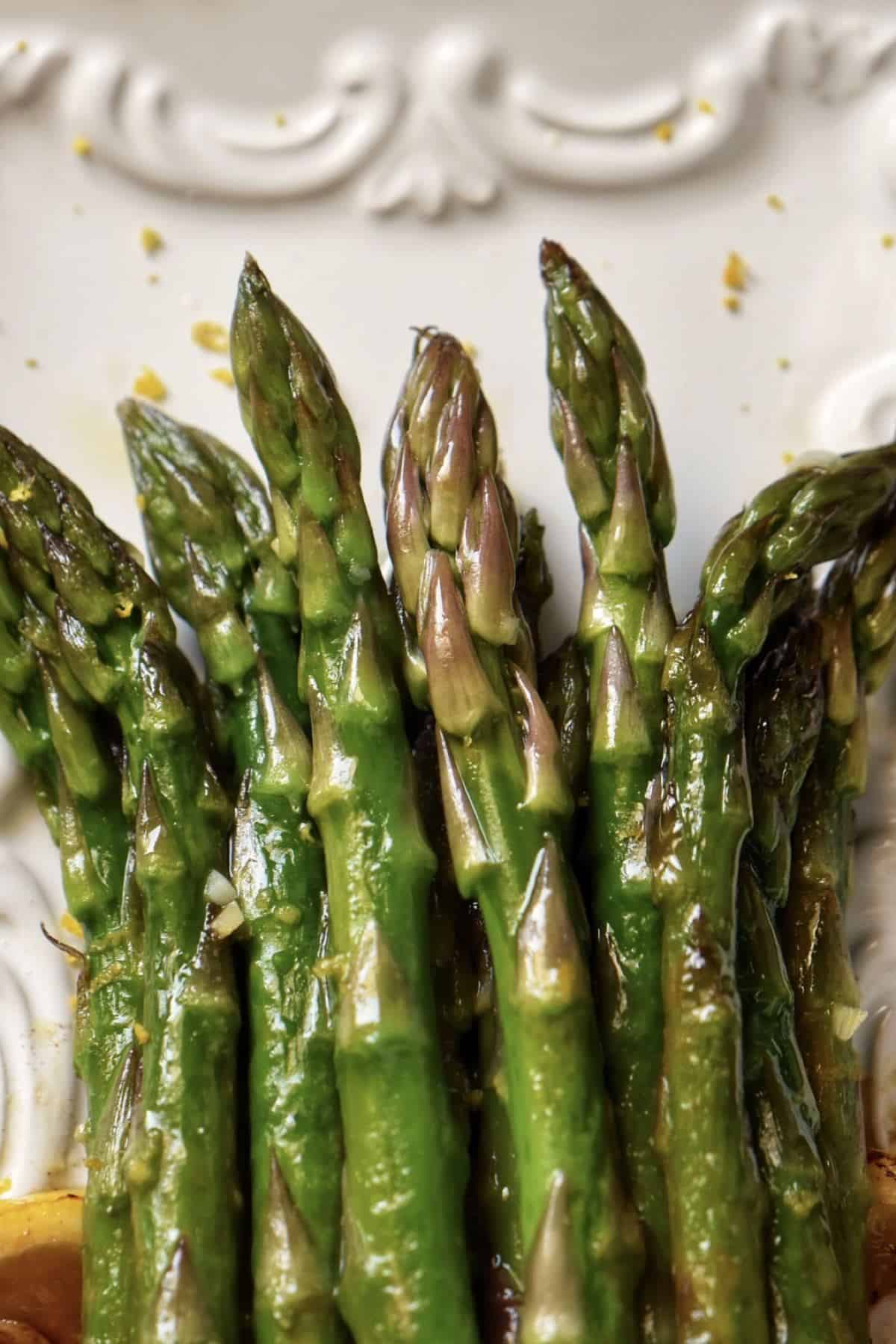 A white platter with lemon and garlic asparagus.