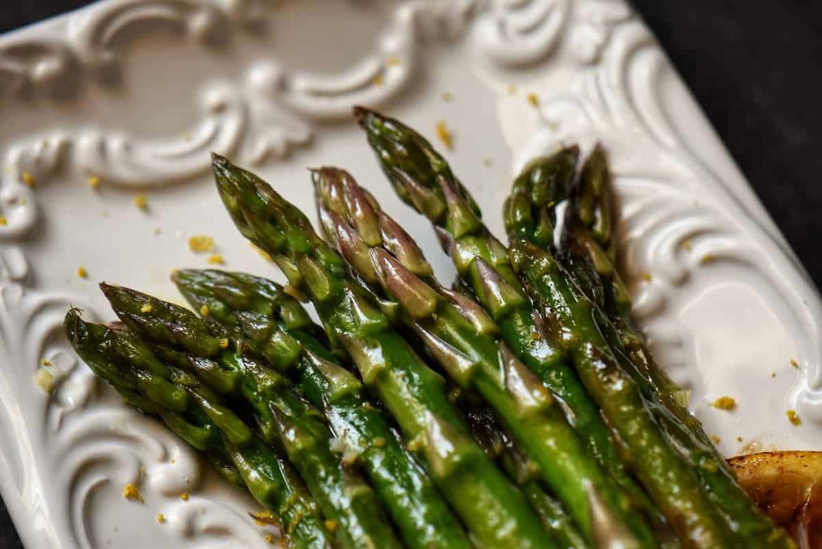 An overhead shot of asparagus tips garnished with lemon zest.