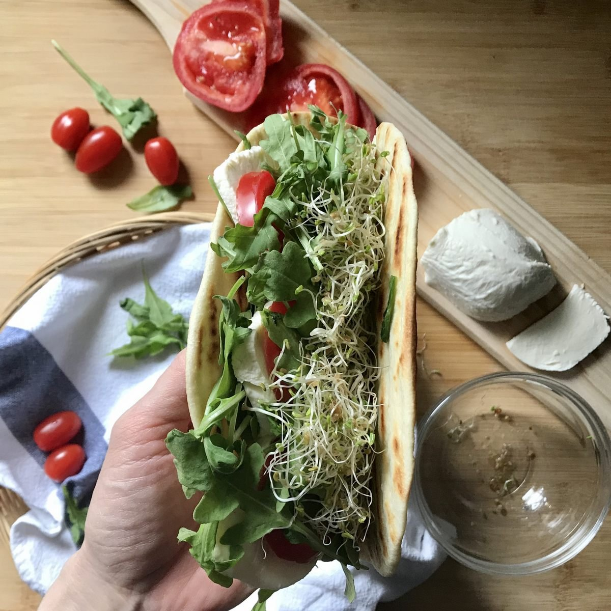A hand held Italian flatbread with vegetables and alfalfa sprouts.