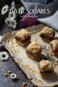 Date squares on a rectangular tray, surrounded by daisies.