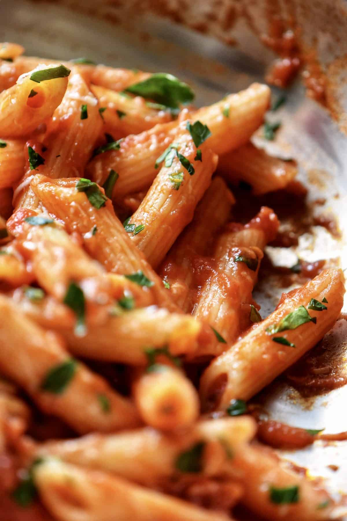 Spicy Penne all'Arrabbiata  in a pan garnished with chopped parsley.