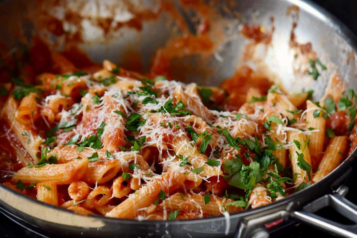 An Italian pasta recipe with Arrabbiata sauce garnished with grated cheese and parsley.
