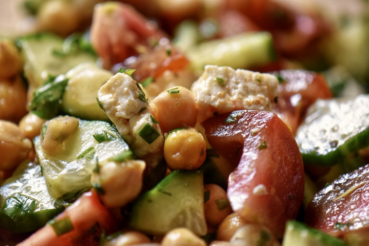 A close up of chickpeas, chopped cucumbers and tomatoes tossed together.