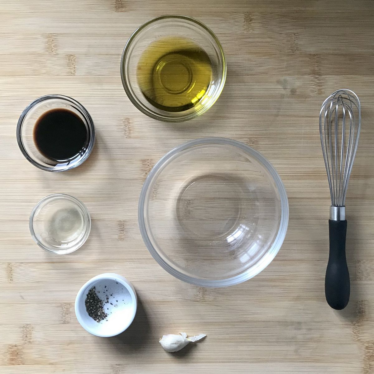 The ingredients to make the vinaigrette in bowls.
