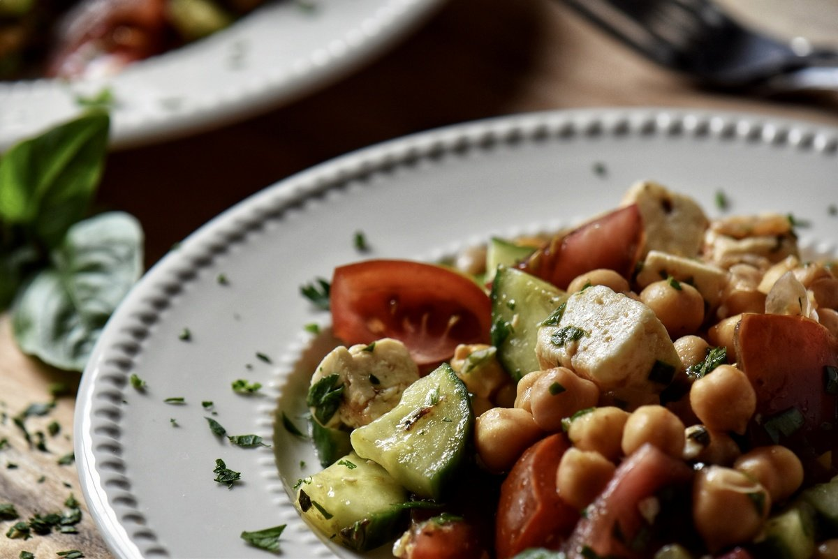 Chickpea salad in a white dish garnished with fresh parsley.