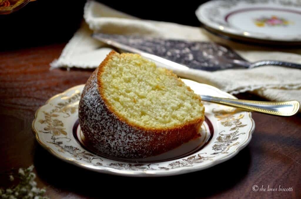 A slice of an Italian lemon cake called ciambella on a cake plate.