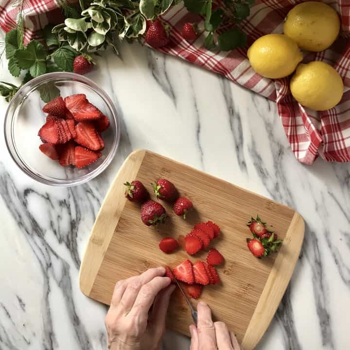 Strawberries being sliced and placed in a bowl.