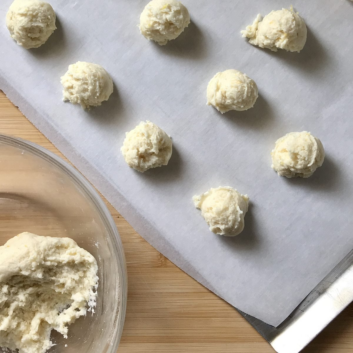 Balls of cookie dough on a parchment lined cookie sheet.