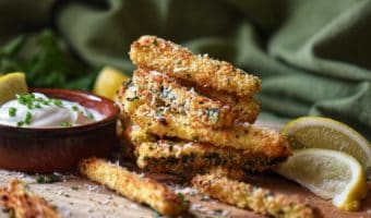 Herb encrusted zucchini on a wooden board.