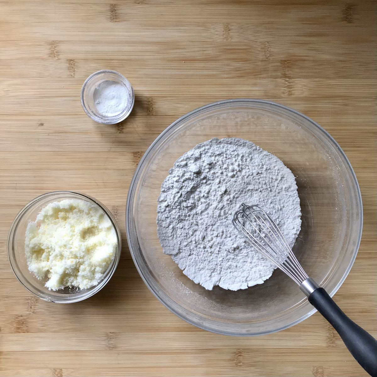 The dry ingredients to make ricotta cookies on a wooden board.