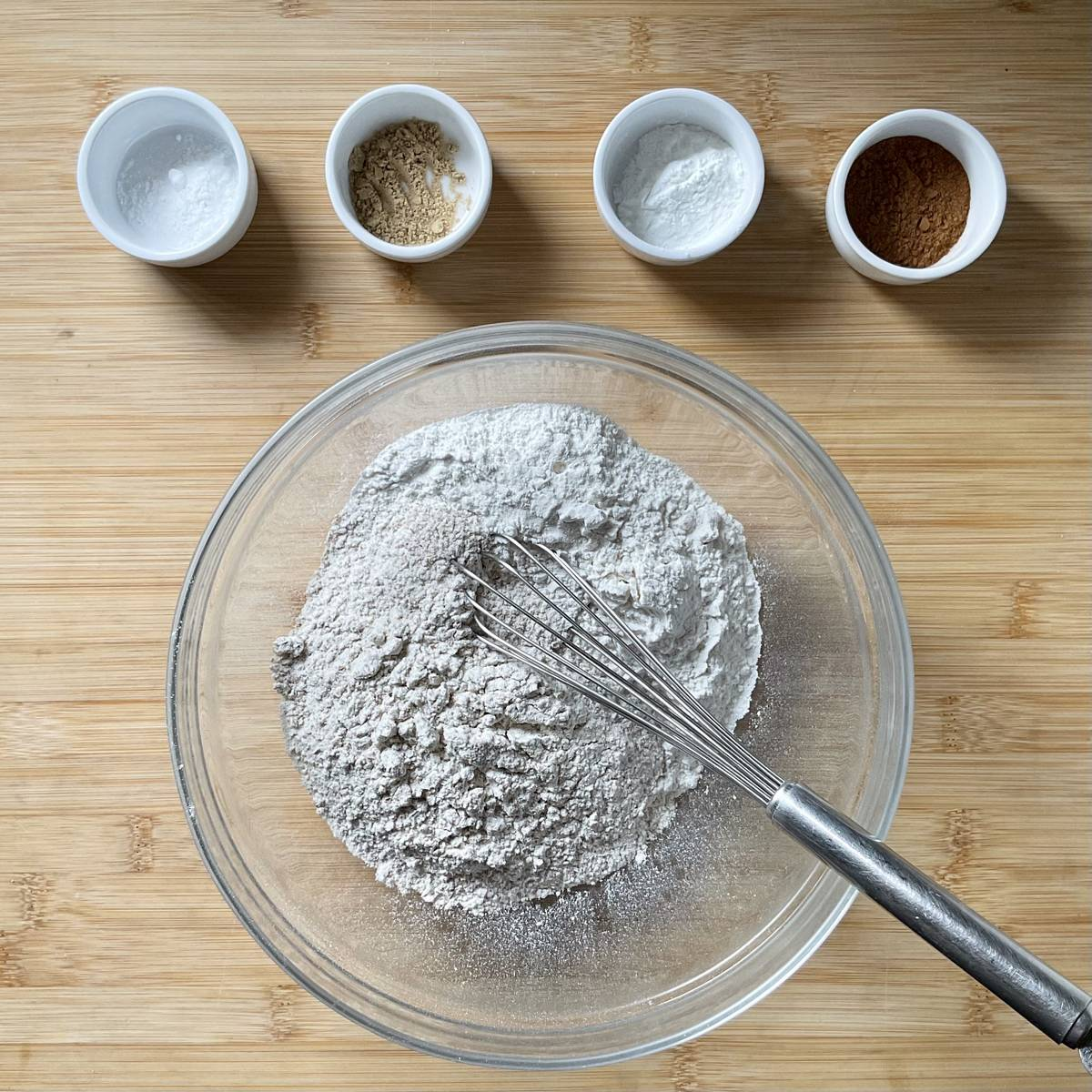 Dry ingredients to make zucchini muffins are on a wooden board.