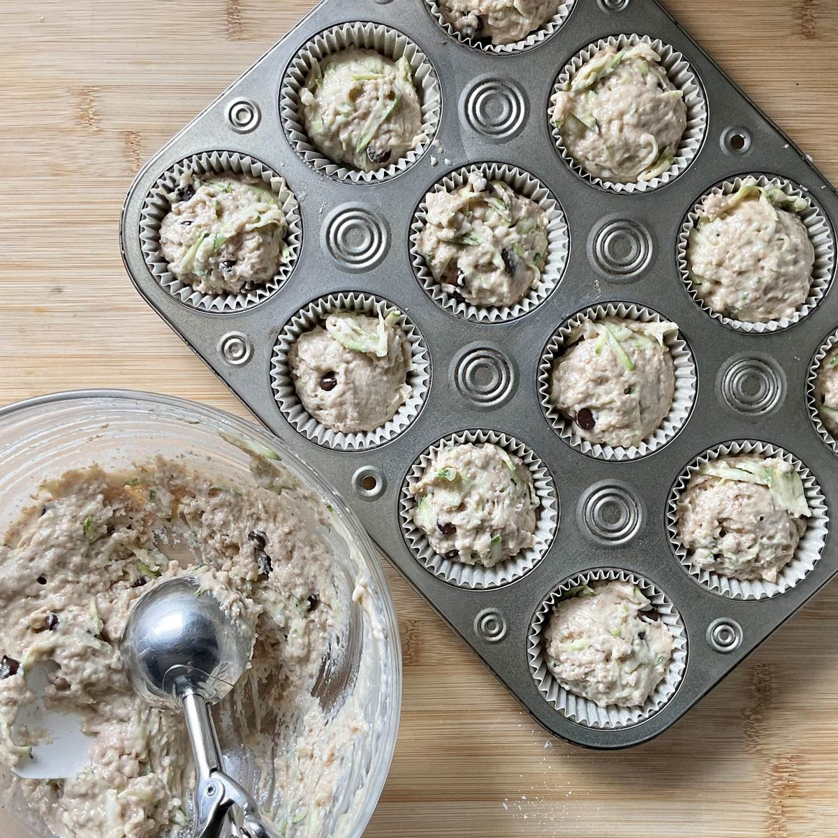 The zucchini muffin batter is being portioned in the muffin tins.