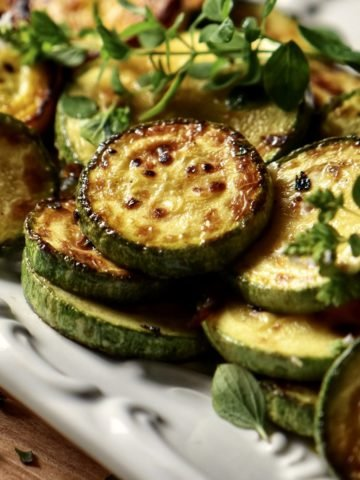 Yellow and green Italian Zucchini on a white serving tray.